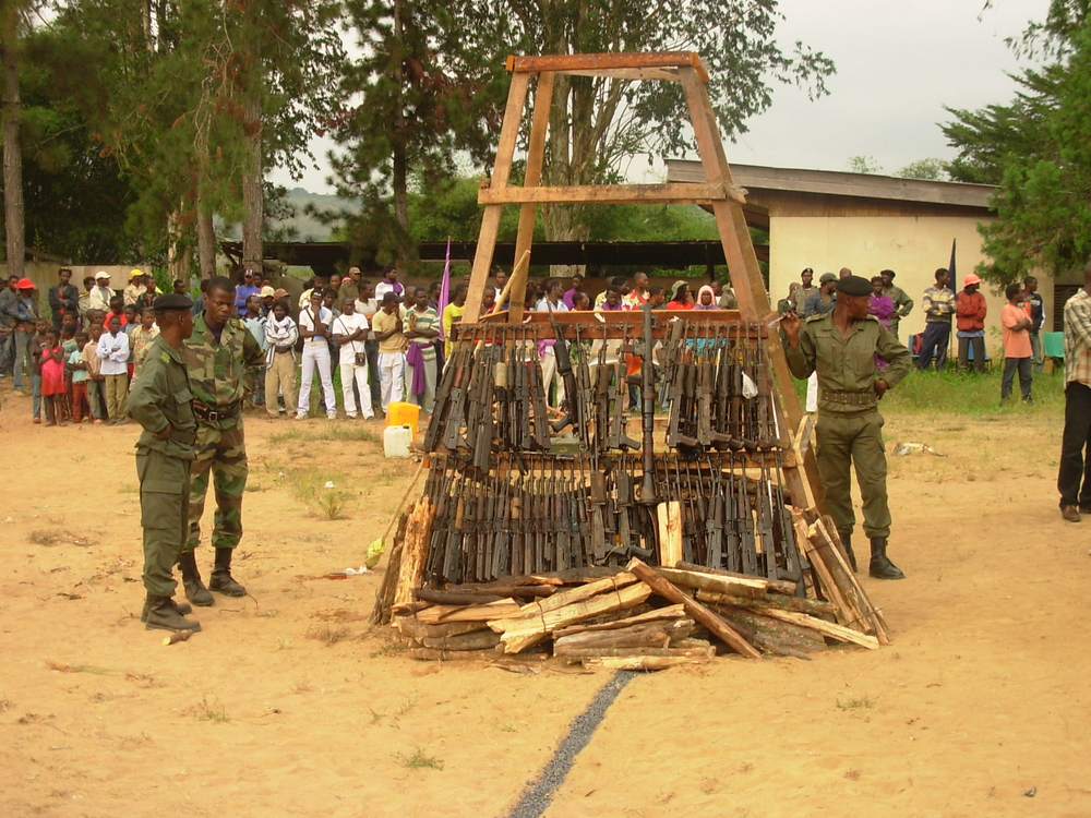 Guards stand next to illegal weapons before the bonfire, Kinkala, south of Brazzavile, at a ceremony to destroy weapons formerly used by his Ninja militias, Congo, 8 June 2007.