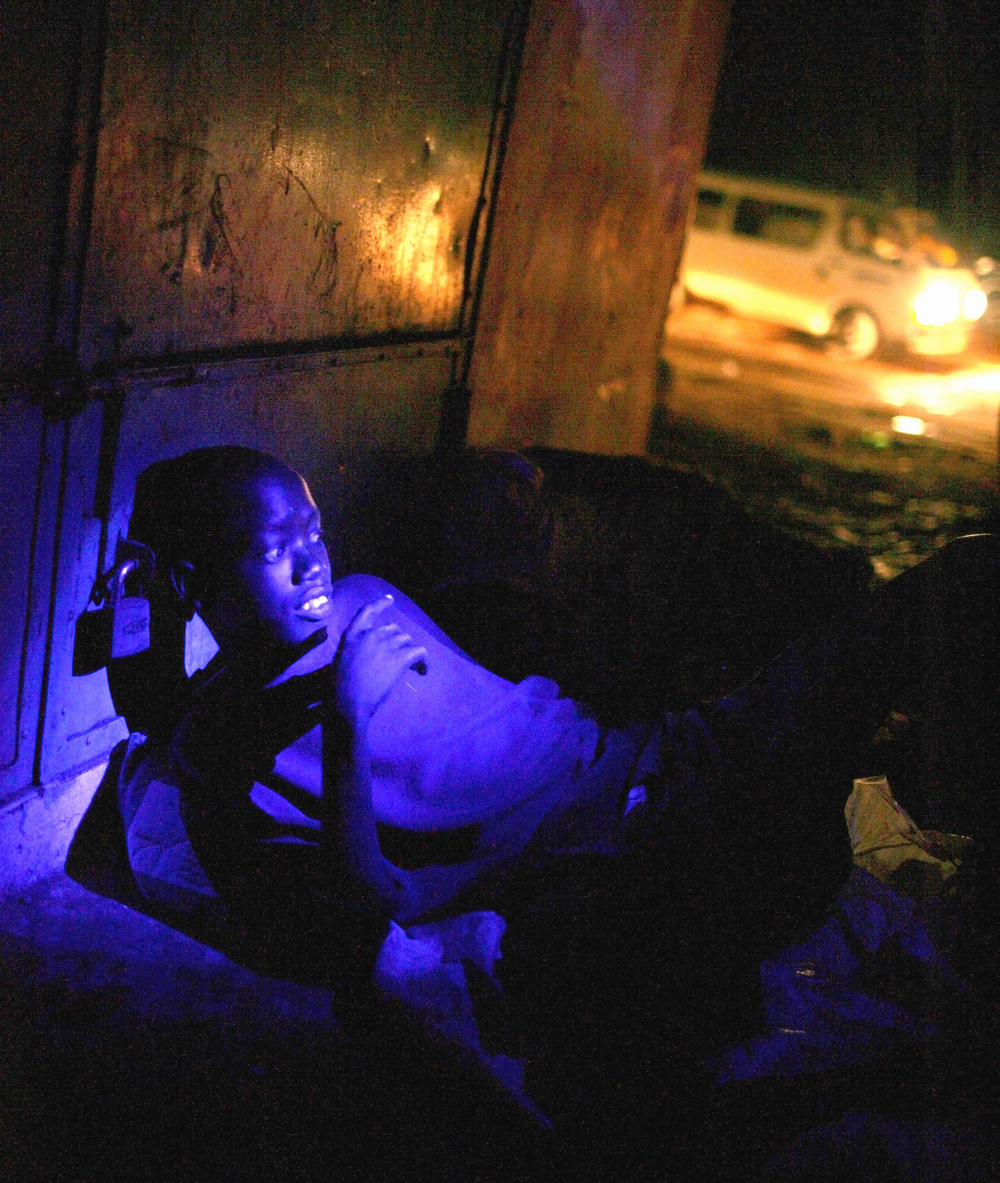 A street boy sleeps rough in one of Juba's markets. Sudan June 2007.