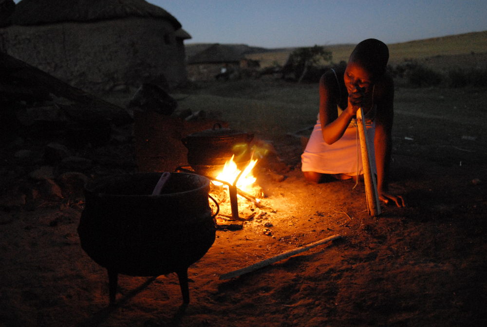 Lineo Makojoa, 15, cooks dinner at her home in Ha Majoro Village in Lesotho. Orphaned by HIV and Aids, she often cooks dinner for her grandparents and her older brother.