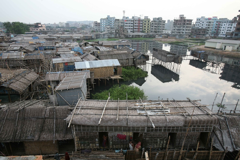 High rise buildings tower over the makeshift houses in this slum, near the Buriganga River, Dhaka, Bangladesh, July 2007. The level of urbanisation in Bangladesh is comparatively low, but the pace is high, ranging from seven to 11 percent in the past five