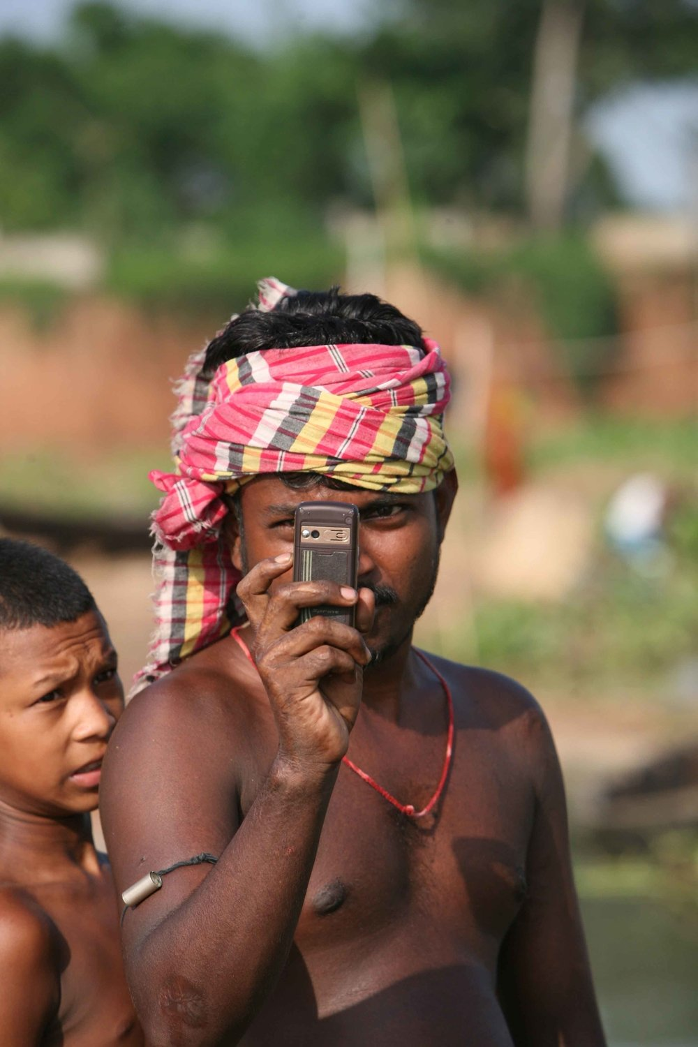 A slum resident takes a snap shot with a mobile phone, Dhaka, Bangladesh, July 2007. 56 percent of the city's population live in slums and slum-like conditions.