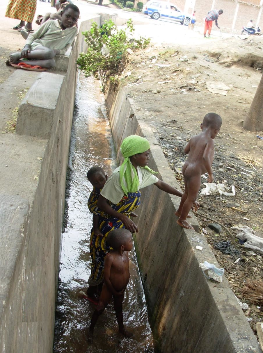 A Congolese woman asylum seeker washes her children with sewer water, outside UNHCR office in Bujumbura, Burundi, 20 August 2007. the Congolese asylum seekers fetch the dirty water for drinking.
