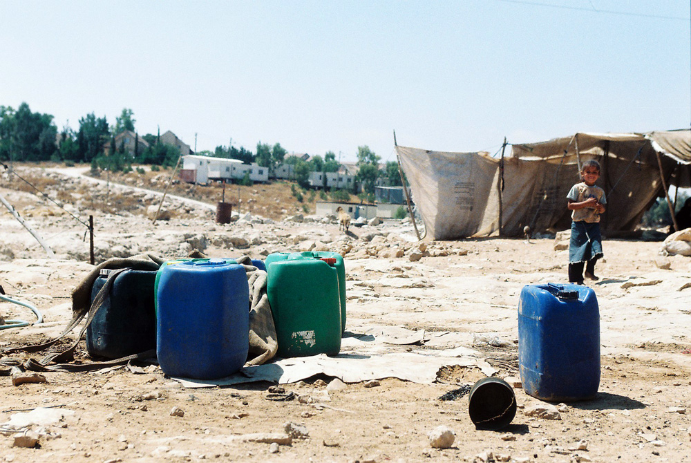Water containers used by the villagers in Um al Khir. Carmel settlement can be seen in the background