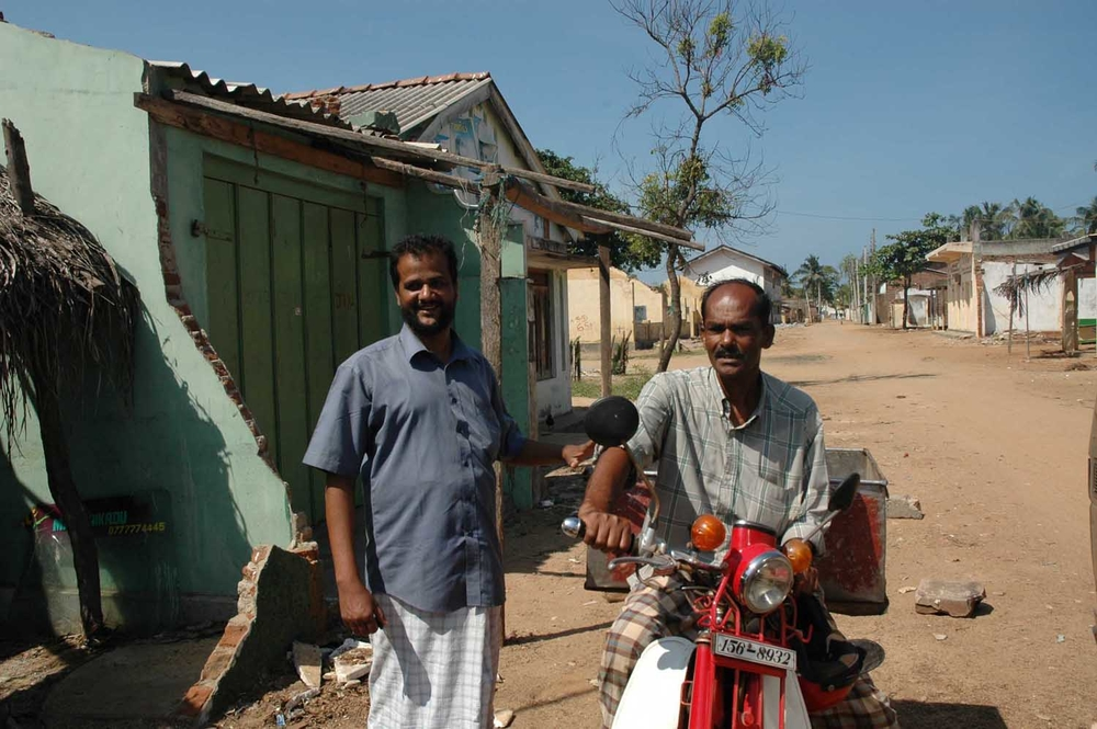 Mohideen Ajeemal, left, with a friend in front of his rebuilt house. The Muslim fish wholesaler from the coastal village of Sainathimaruthu in Ampara District, eastern Sri Lanka, lost his house to the December 2004 tsunami. On 12 September this year, when