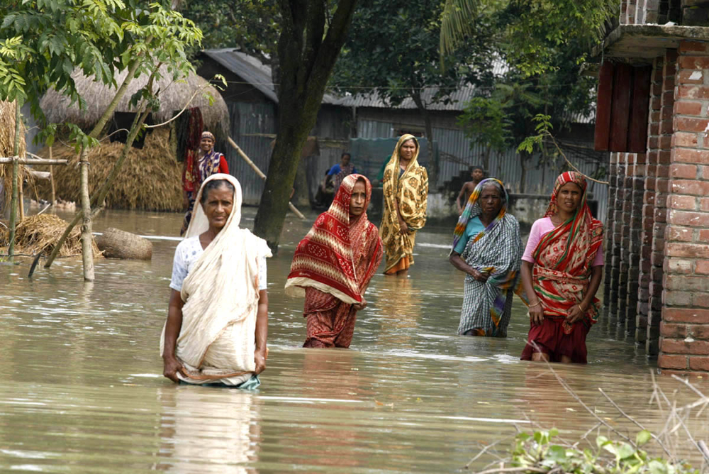 Waters still are rising in Bangladesh's south-central Ullapara region. These women are heading for the nearby flood shelter established by the government. Bangladesh, September 2007.