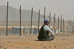 [Jordan] A refugee sits near the fence of Rweished camp, 50 km off the Jordanain Iraqi border. [Date picture taken: 11/06/2006]