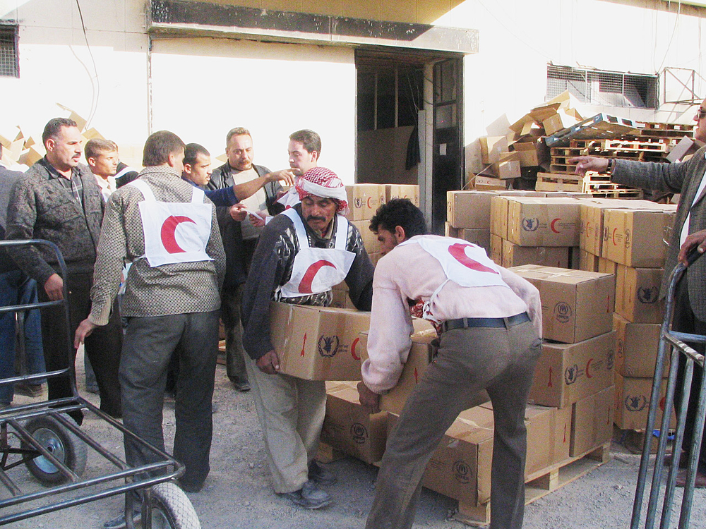 Red Crescent volunteers unload food aid for Iraqi refugees at a centre in Damascus.