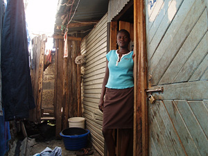 [Kenya] sex worker (Lillian Baraza) in Kibera standing next to the door of her house. She is 17 years old and men come to her house for sex so she sits all day as men walk in and out. [Date picture taken: 02/04/2007]