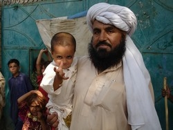 [Pakistan] A father along the border between Afghanistan and Pakistan awaits to have his son vaccinated against polio. The virus remains endemic in both countries. [Date picture taken: 03/22/2007]
