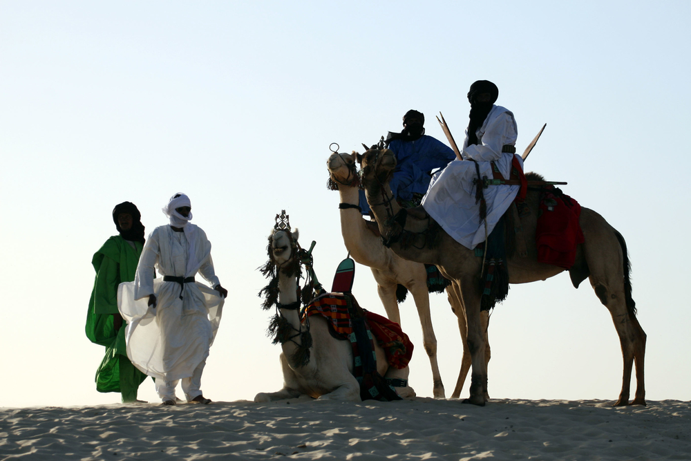 A group of Tuareg men in traditional dress silhouetted on the crest of a sand dune at an oasis, west of Timbuktu, Mali. February 2008. Many Tuareg nomads still lead salt caravans across the desert to the market in Timbuktu. Tuaregs are spread across five