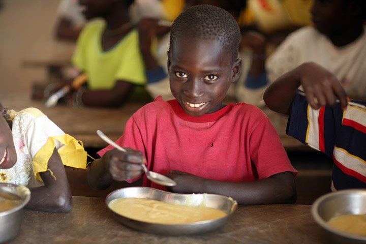 A boy smiles while eating donated food by WFP in Eva Orango school in Orango Island of Bijago Archipelago in Guinea-Bissau Feburary 2008. According to World Food Program (WFP) intellectual levels rise when children are fed properly.