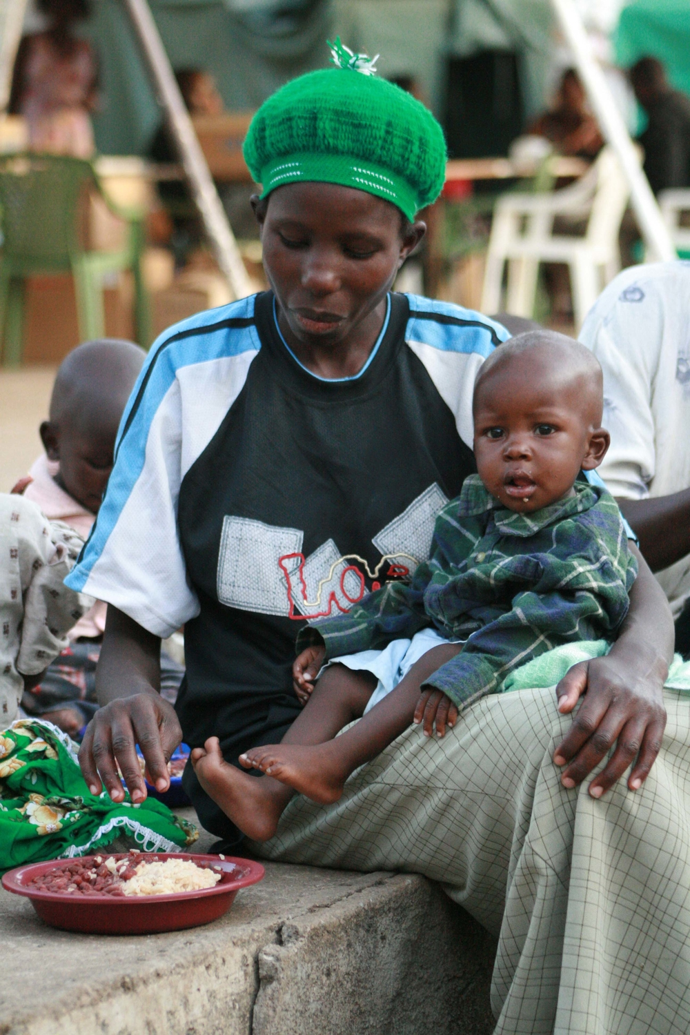 A displaced woman with her child shares a meal in Kisumu, February 2008.