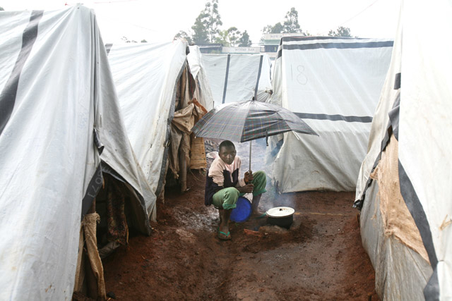A young boy makes a meal outside as it rains in the Eldoret IDP camp, Kenya. April 2008. The camp has over 14,000 displaced persons.