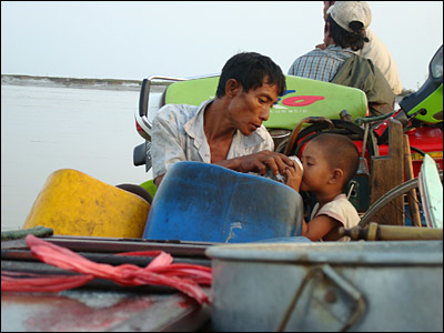 A father giving his son something to drink as they sit on board a ferry. Lack of safe drinking water is a major problem and reports of diarrhoea are increasing.