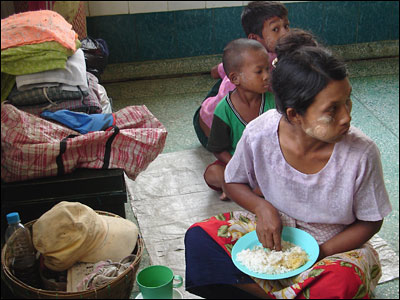 A hungry woman grabs her first meal in a long time at a Yangon shelter housing hundreds of people, which is being supported by Myanmar Red Cross.