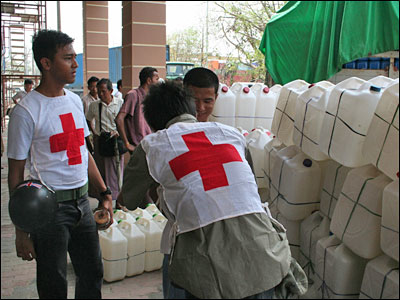 Myanmar Red Cross volunteers loading water storage containers onto a truck. Families can use these along with water purification tablets to have clean drinking water.
