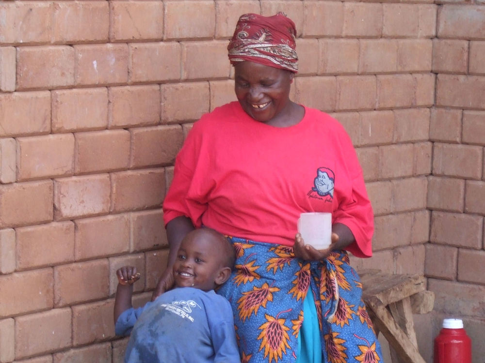 Two-and-a-half year old Tito, the Nyumbani village's youngest resident, with his grandmother outside their home.