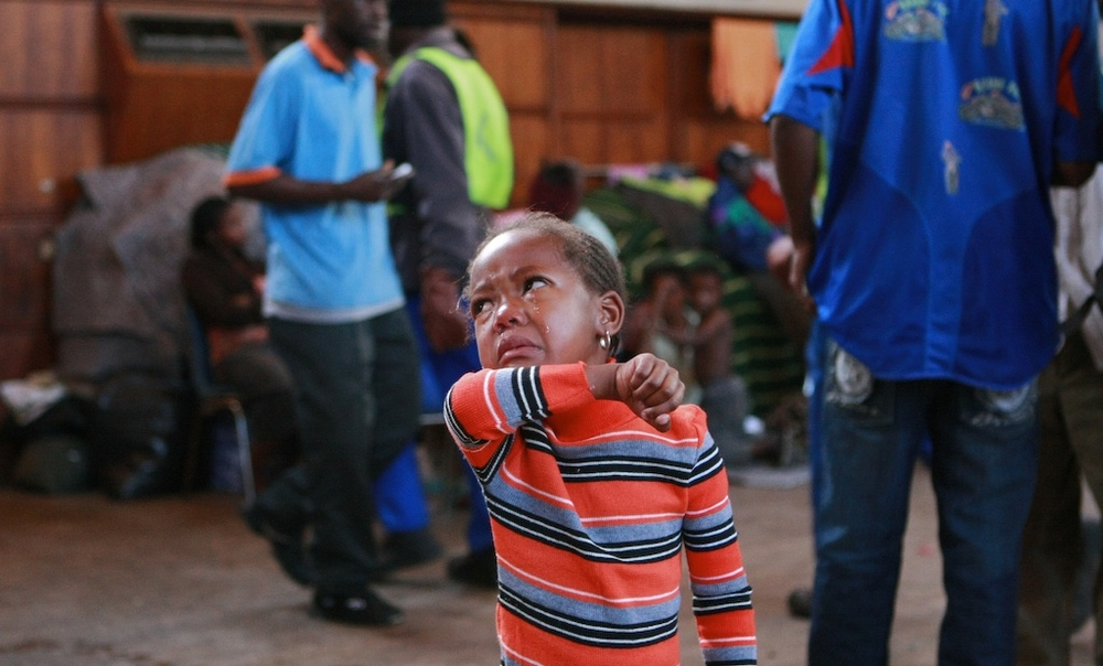 A child of Mozambique national cries as she searches for her mother at Germiston city hall, they have been refugees in the hall after recent xenophobic attacks on foreigners around the country. South Africa. June 2008.