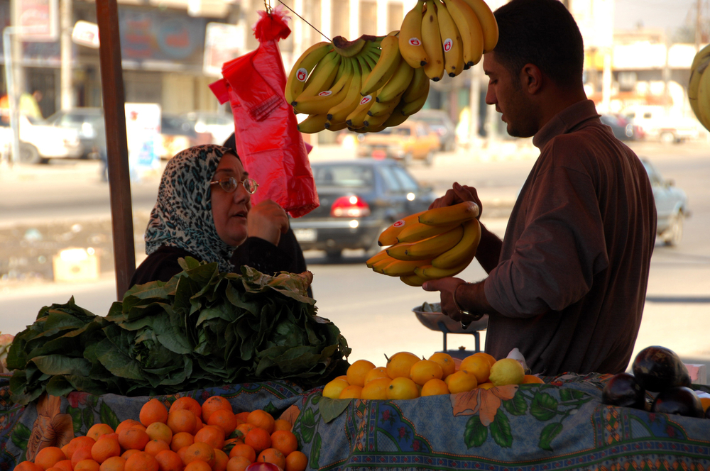 An woman buys fruit in a market in Baghdad. The new food rationing system will exclude those with high incomes.