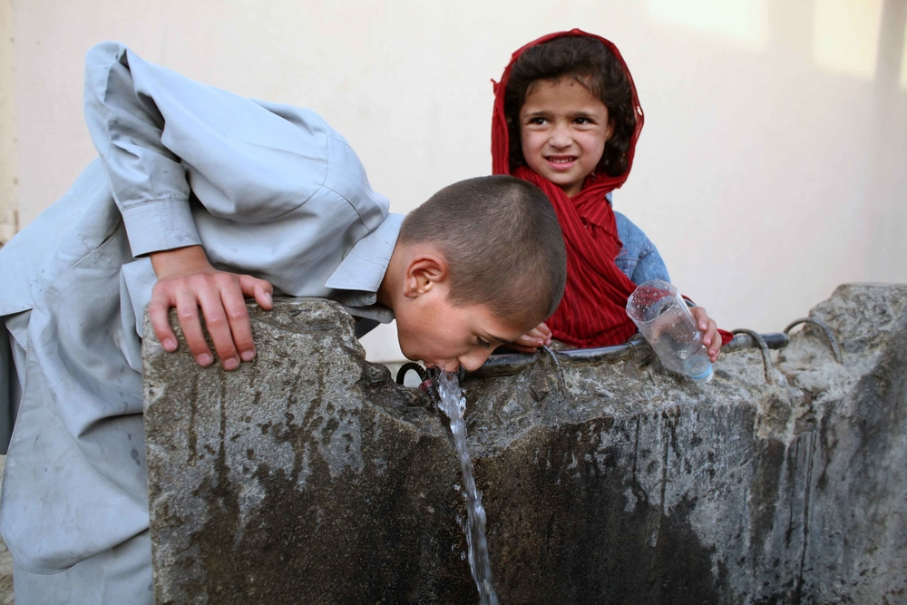 A boy drinks water from a common tap  in Western Kabul, Afghanistan, June 2008.