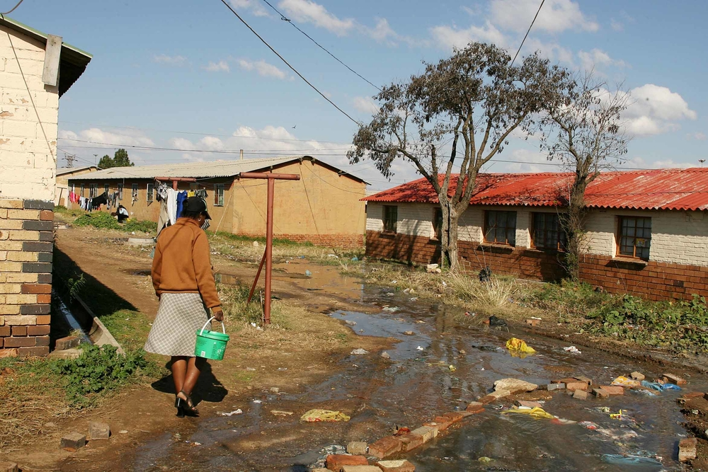 Formally a single-sex hostel under Apartheid, the Dube Hostel in Soweto, South Africa is being turned into family townhouse units however as construction on the new units continues, residents are largely left without sanitation and electricity. This woman