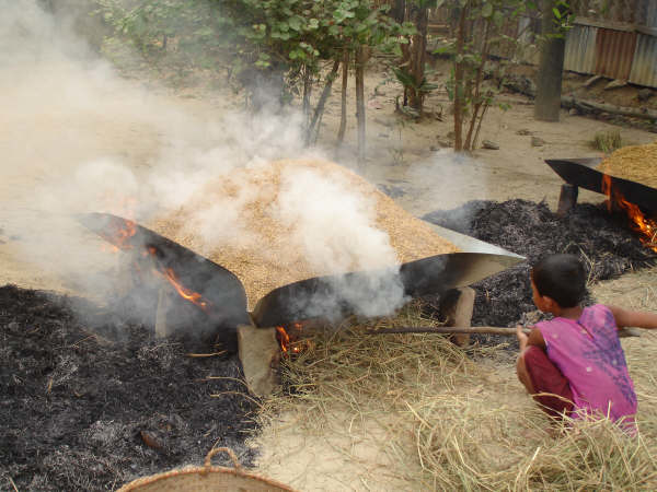 Children are exposed to harmful smoke even outside the kitchen. Photo shows a girl helping her mother parboil newly harvested paddy in Kolapara in Bangladesh's southeastern Feni District.