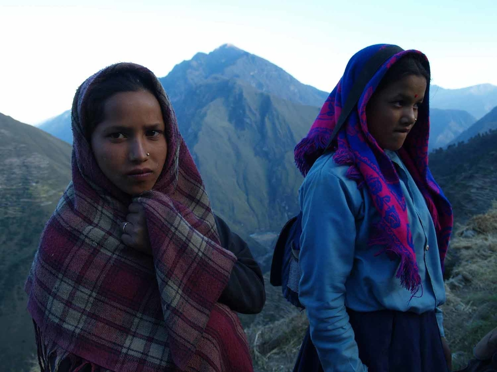 Young girls return home from school in Maila, Humla District, Mid-West Nepal. Many students trek on an empty stomach two to three hours over steep terrain to get to and from school and are left little time to study.