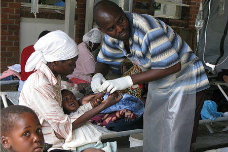 A nurse taking care of a child cholera patient