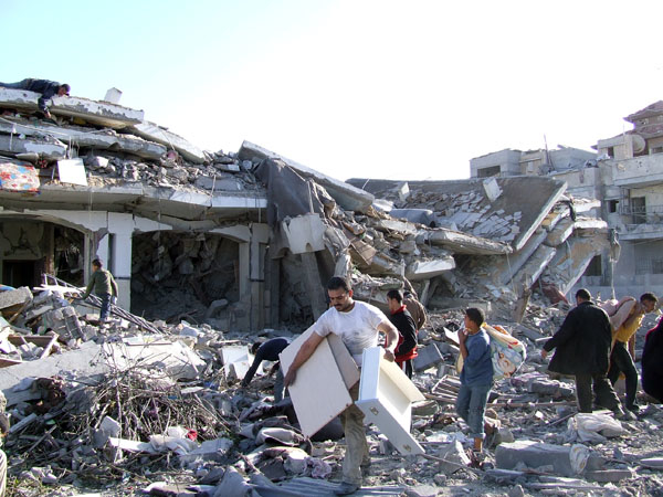 Rafah town residents salvage what they can from the rubble of their homes after Israeli airstrikes in the Gaza Strip
