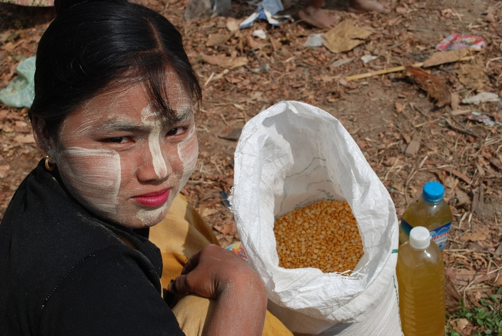 A young Burmese in Myanmar's Ayeyarwady Delta alongside a bag of pulses