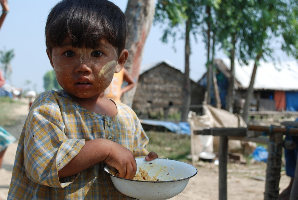 A young child grasps a bowl of food in Myanmar's Ayeyarwady Delta