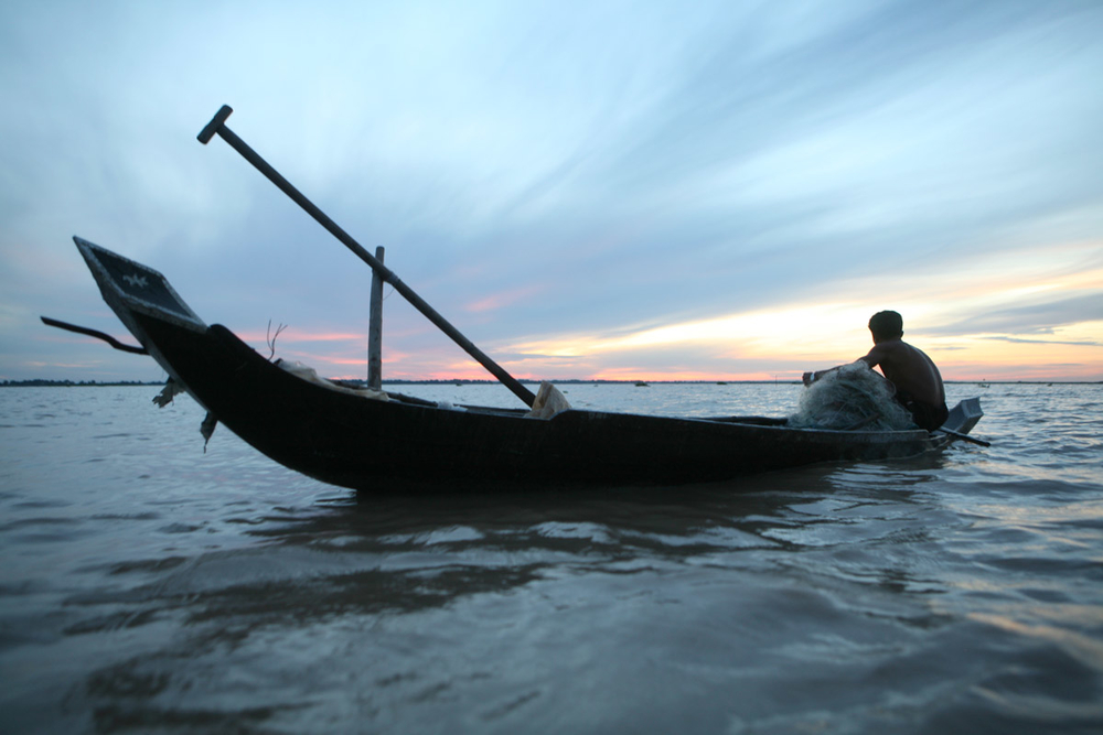 A fisherman plying his trade on the waters of the Tonle Sap lake, Cambodia. The lake is Cambodia's largest and provides income to tens of thousands of families but the traditional fishing industry here is under threat from climate stresses and commercia