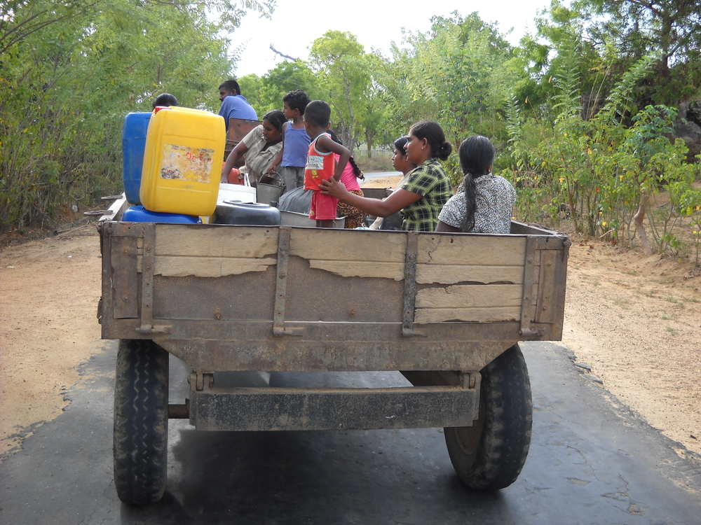 People transporting water on tractor trailer in Sri Lanka's Ampara District