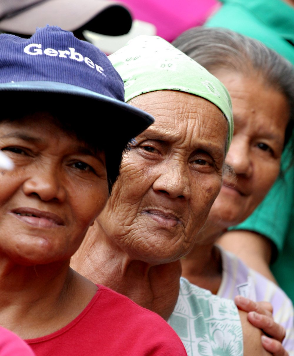 Manila - Elderly women queue to receive relief items and sanitary packs from the International Organization of Migration in the lakeshore community of Muntinlupa, outside Manila, where many villages remain under water five weeks after tropical storm Ketsa