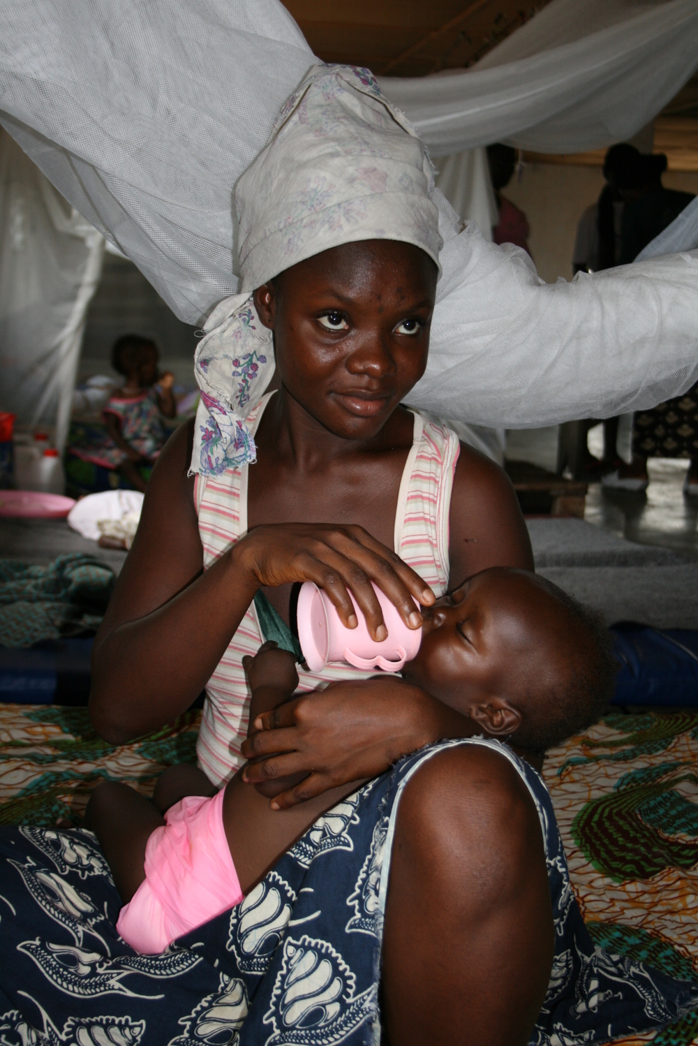 Mamie Masako, 19 feeds her baby at the VOA therapeutic feeding centre for severely acutely malnourished children, run by ACF