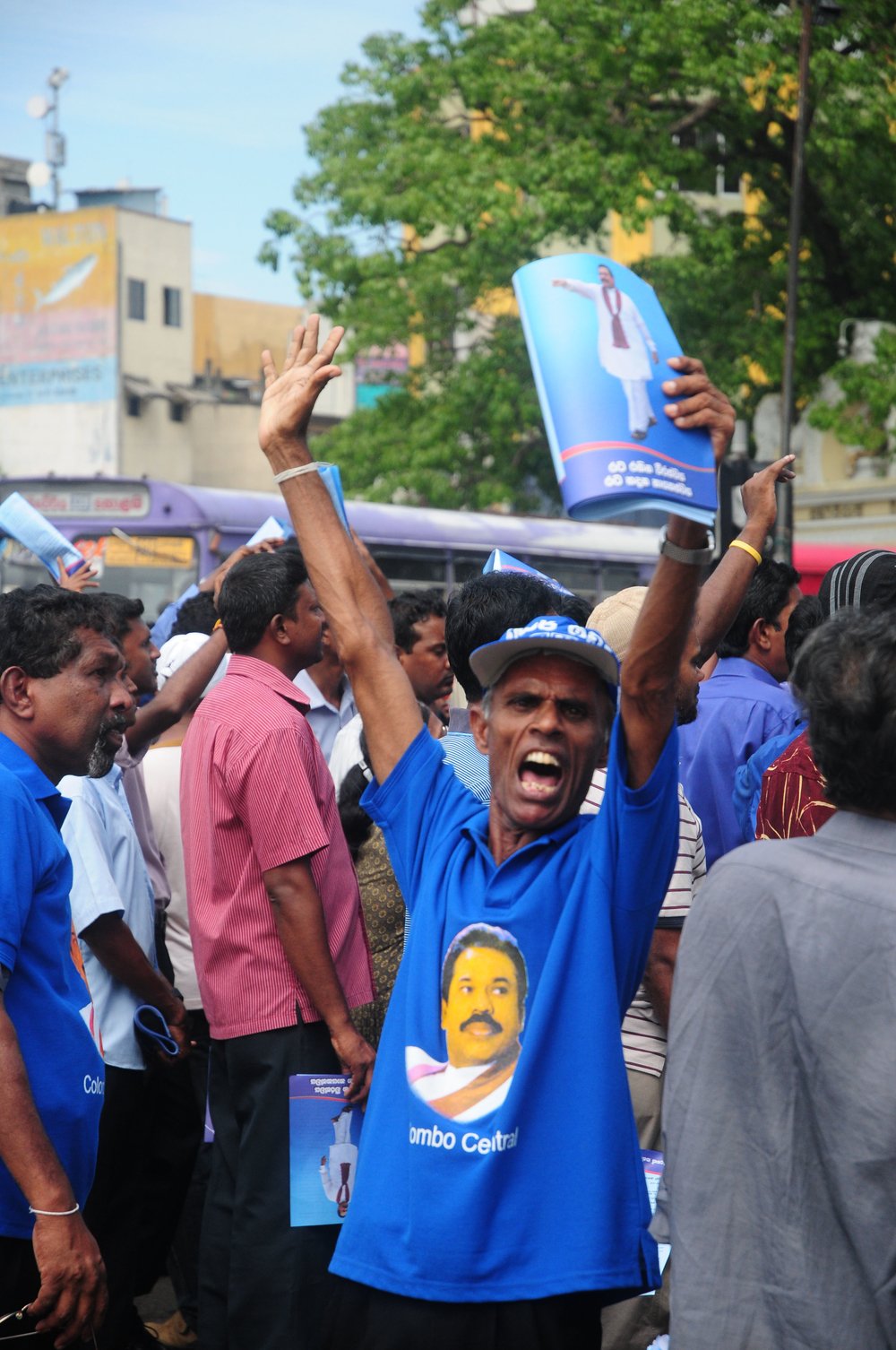 Supporters of President Mahinda Rajapaksa take to the streets wearing his party colours, chanting slogans and distributing propaganda material