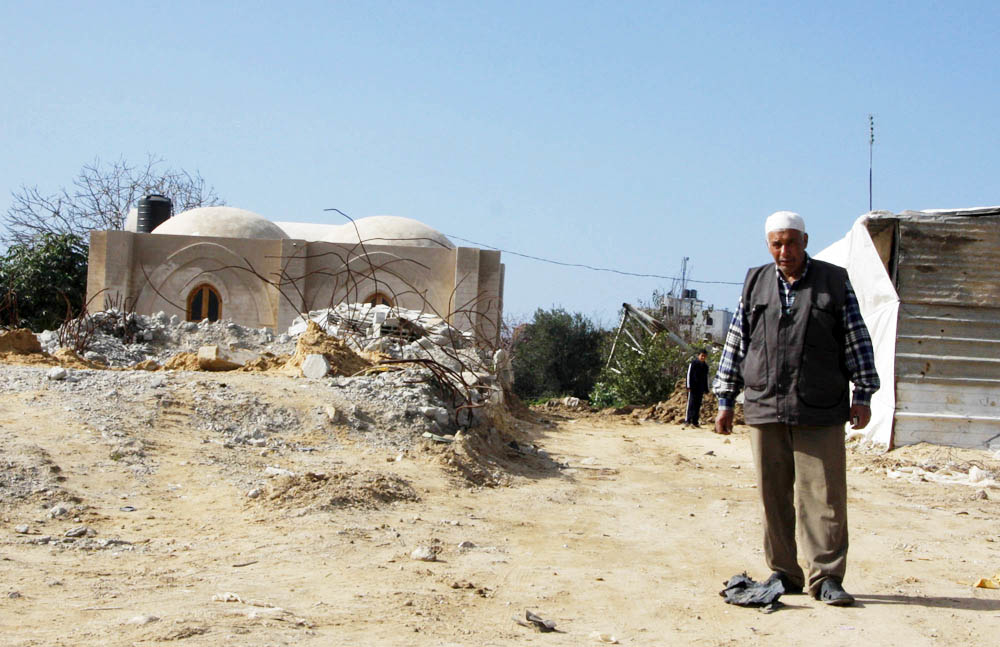 Hassan al-Err, 66, stands outside his new mud-brick house in eastern Jabaliya, Gaza. His family had been living in a tent for the past year since their home was destroyed in Israel's war in Gaza