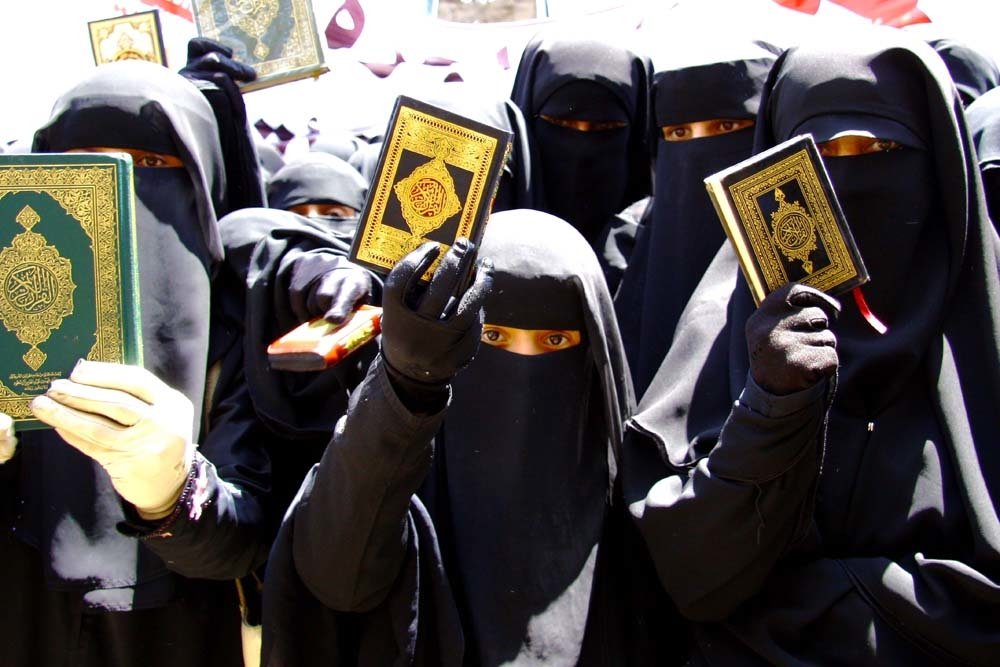 Women protesters hold up copies of the Quran outside parliament in Sanaa while stating that a proposed law banning marriages under the age of 17 in Yemen is un-Islamic