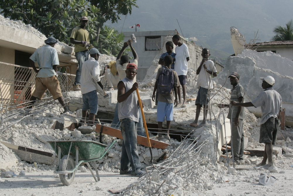 Youths cleaning up earthquake rubble at what was once a church/school building in the Martissant neighbourhood of Port-au-Prince. March 2010