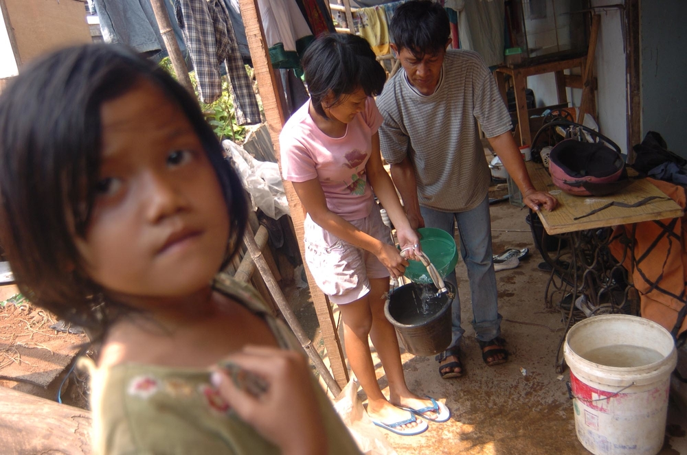 Family members transfer water from one pail to another. Clean water and sanitation are key concern in Jakarta's slums