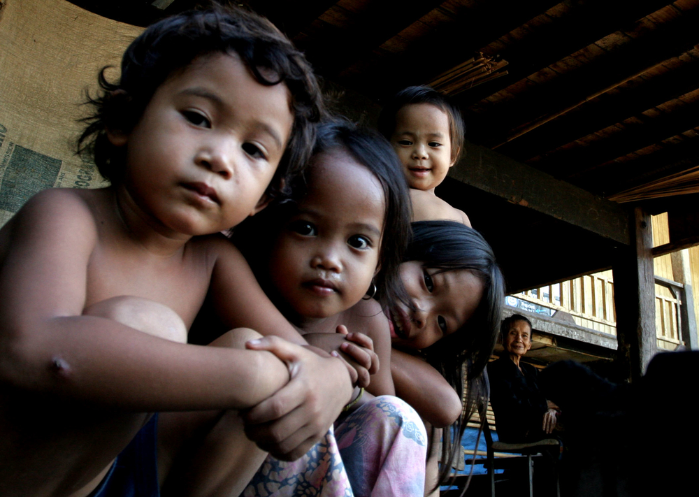 Datu Piang - Payuna Biano, 59, (far right) poses for an unlikely family portrait with four of her young grand children while living in a cramped crawlspace beneath a school in the southern Philippine town of Datu Piang in Maguindanao province. Biano and h