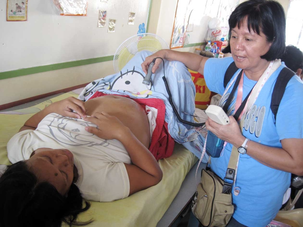 A midwife checks on a pregnant woman at an evacuation centre during a UNFPA medical mission. Midwives provide crucial maternal care to women in geographically isolated and disadvantaged areas where doctors and nurses are scarce