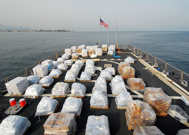 Pallets of humanitarian assistance supplies sit on the flight deck of USS McFaul (DDG 74) before the transfer of the supplies off the ship