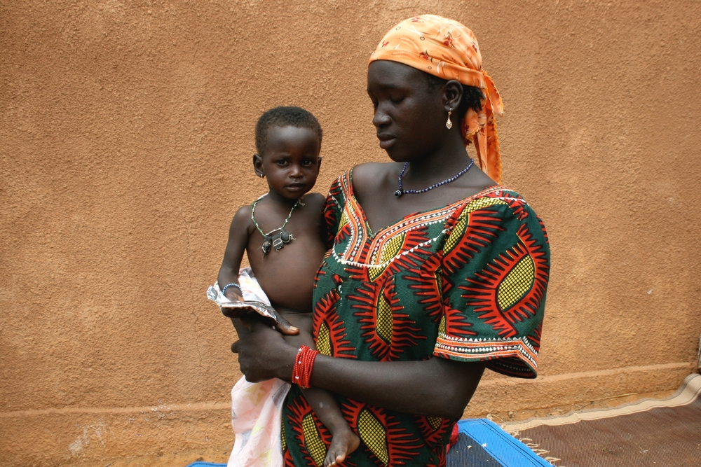 Severely malnourished children in Tahoua, Niger, holding a packet of Plumpy'nut