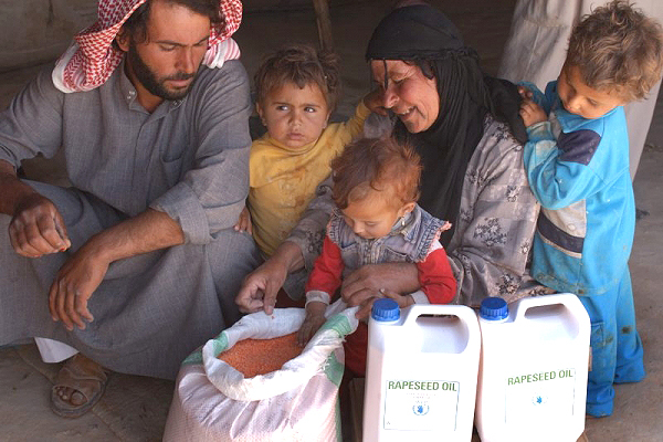 A Syrian family receives food aid at a WFP distribution point (file photo)