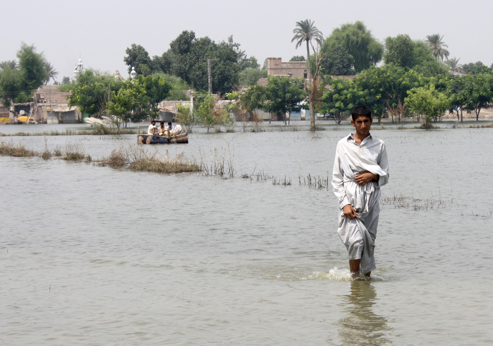 A man wades through flooded fields in Reikhbaghwala village in Pakistan's Punjab province