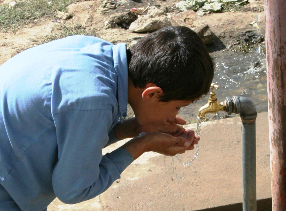 A boy drinks water from a tap outside a school in Kabul