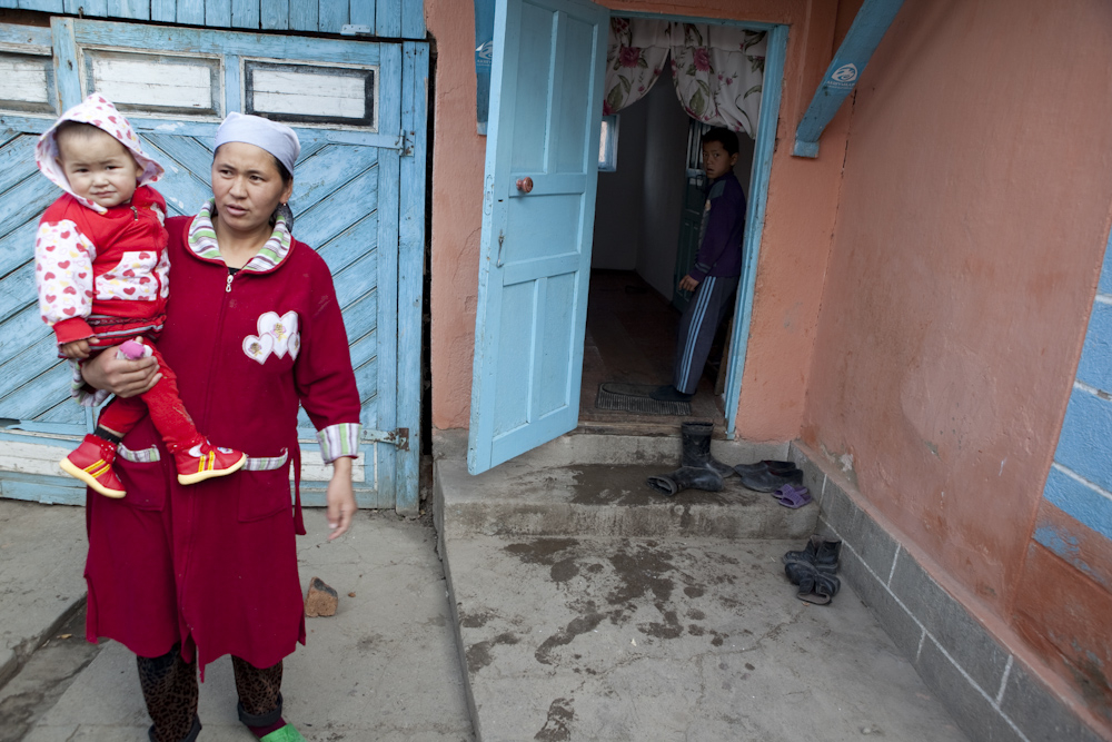 Jazira Seitaliyeva holds 18-month Fatima outside their home in Ak-Korgon. Fatima began walking at 11 months, earlier than any of her five siblings. Her 10-year-old brother, standing in the doorway, has cerebral palsy; he started walking only when he was t