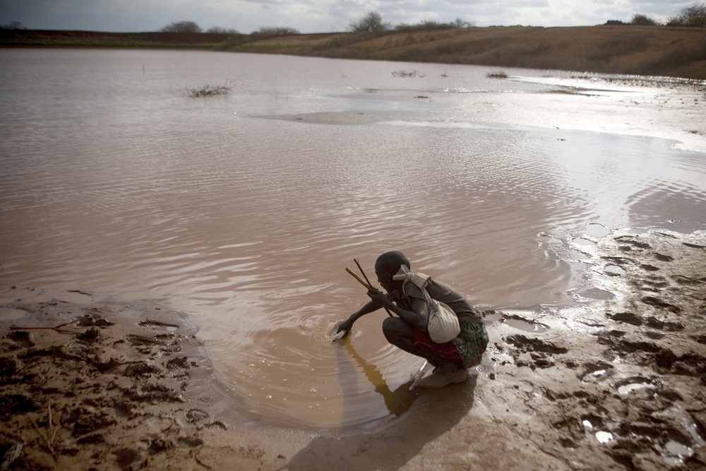A man drawing water from a reservoir near the border town of Moyale
