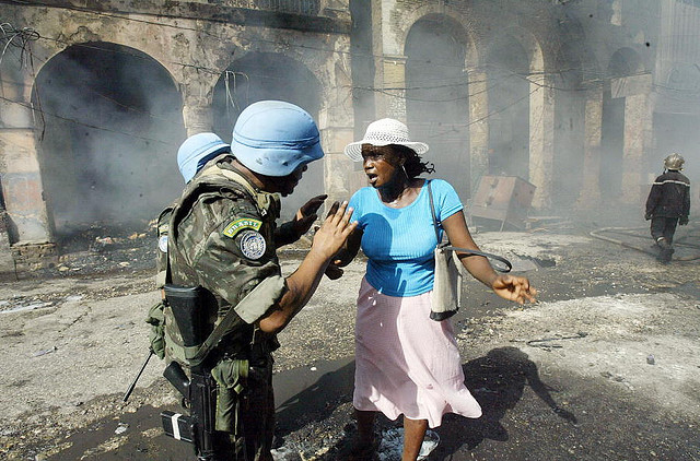 United Nations Stabilization Mission in Haiti (MINUSTAH) peacekeepers helping a street merchant in the downtown area of Port-au-Prince after a fire that ravaged 50 stores on 23 June 2004. Troops from the Brazilian contingent helped the Haitian National Po